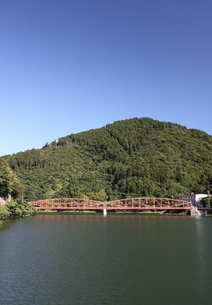 湖にかかるピンク色の鉄橋と山と青空の写真素材 [FYI00143631]