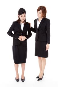 腹痛の同僚を心配するビジネスウーマンの素材 [FYI00144269]