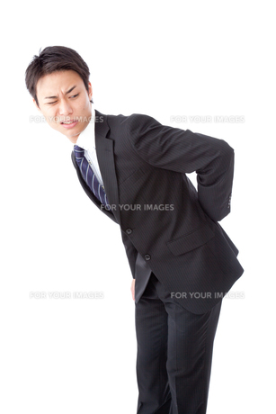 腰痛で苦しむ若いビジネスマンの写真素材 [FYI00144270]