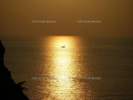 黄金色の夕焼けに包まれる一艘の船の写真素材 [FYI00145472]
