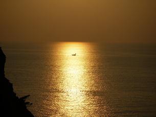 黄金色の夕焼けに包まれる一艘の船の素材 [FYI00145472]