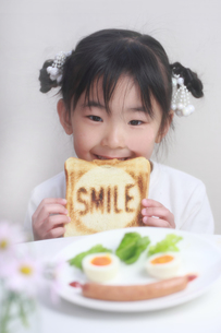 笑顔でパンを食べる少女の写真素材 [FYI00149694]