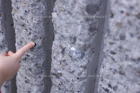 コンクリート壁を指差す子供の手の写真素材 [FYI00166664]