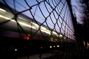 フェンス越しの電車の写真素材 [FYI00175595]