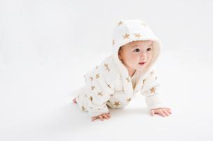 星柄の冬服を着たハイハイする赤ちゃんの写真素材 [FYI00176827]