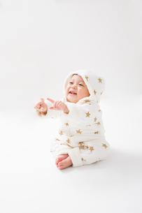 星柄の冬服を着た座っている赤ちゃん・縦の写真素材 [FYI00176828]