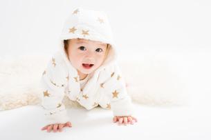 星柄の冬服を着たハイハイする赤ちゃんの写真素材 [FYI00176833]