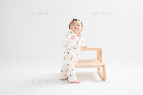 台につかまり立ちして振り返る赤ちゃんの写真素材 [FYI00176837]
