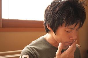 タバコを吸う若い男性の写真素材 [FYI00177624]