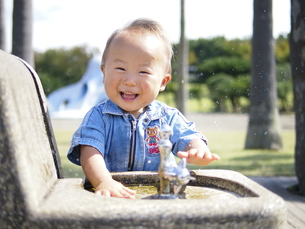 笑顔で水道のイタズラをする子供の写真素材 [FYI00180777]