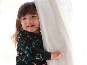 カーテンでかくれんぼする女の子の写真素材 [FYI00180801]