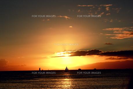 ハワイの海に沈む夕日とヨットの写真素材 [FYI00180901]