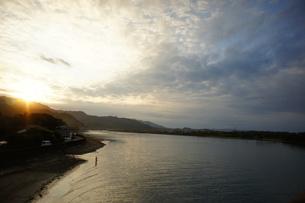 河口の夕陽と釣り人の写真素材 [FYI00186549]