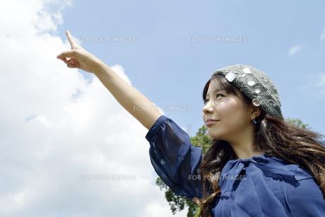 青空を指す女性の写真素材 [FYI00187349]