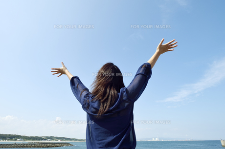青空と両手を広げる女性の写真素材 [FYI00187374]