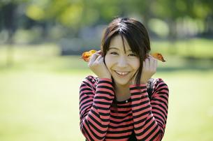 落ち葉を耳にあてる女性の写真素材 [FYI00187375]