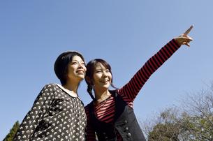 青空と指を指す女性の写真素材 [FYI00187382]