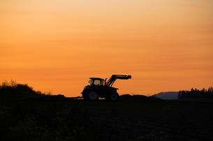 夕暮れの丘の上のトラクターの写真素材 [FYI00189290]