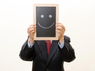 スマイルマークを持つビジネスマンの写真素材 [FYI00200241]