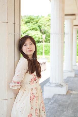 柱に寄りかかる若い女性の写真素材 [FYI00204704]