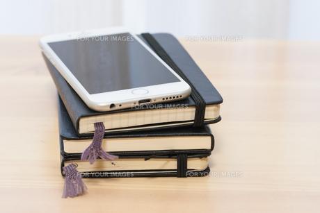 スマートフォンと黒い表紙のノートの写真素材 [FYI00206218]