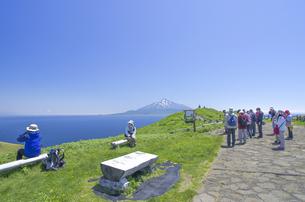 北海道礼文島 桃岩展望台の観光客と残雪の利尻山を望むの写真素材 [FYI00213325]
