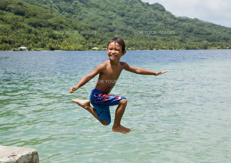 笑顔で宙に浮く少年の写真素材 [FYI00213916]