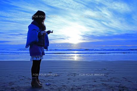 初日の出が浮かぶ海を見つめての写真素材 [FYI00215939]