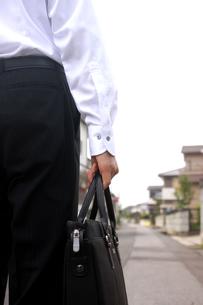 住宅街を歩くビジネスマンの写真素材 [FYI00217592]