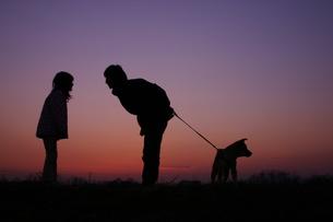 夕暮れの親子と犬のシルエットの写真素材 [FYI00217689]