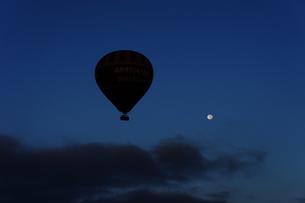 満月をバックに飛ぶ熱気球の写真素材 [FYI00222425]