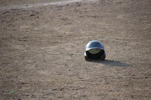 グランドにポツンと置かれたヘルメットの写真素材 [FYI00223456]