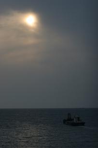 曇り空の太陽と貨物船の写真素材 [FYI00223614]