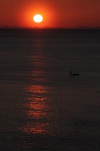 赤い空に昇る太陽と小さな漁船の写真素材 [FYI00223620]