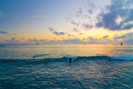 夕日とサーファーたちの写真素材 [FYI00224329]