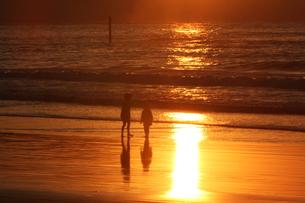 砂浜のオレンジロードを渡る子供たちの写真素材 [FYI00231235]