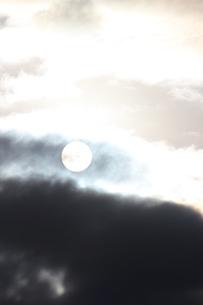 白い雲と雨雲の間から見える太陽の写真素材 [FYI00234211]
