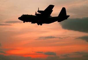 鮮やかな夕焼けを背景に飛行中の米海軍C−130Tハーキュリーズ輸送機の写真素材 [FYI00240353]