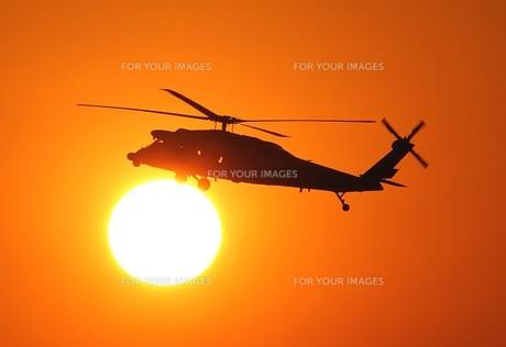 美しい夕焼けを背景に飛行する海上自衛隊のUH-60J救難ヘリコプターの写真素材 [FYI00240386]