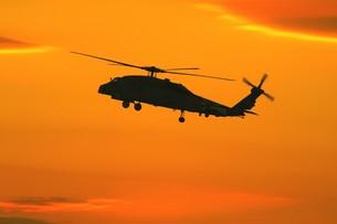 美しい夕焼けを背景に飛行する米海軍のSH-60Bシーホーク対潜ヘリコプターの写真素材 [FYI00240388]
