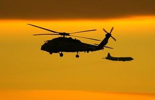 美しい夕焼けを背景に飛行する米海軍のSH-60Bシーホーク対潜ヘリと対向する海上自衛隊のP-3Cオライオン哨戒機の写真素材 [FYI00240389]