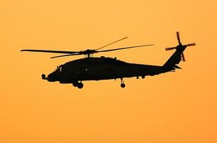 美しい夕焼けを背景に飛行する米海軍のSH-60Bシーホーク対潜ヘリコプターの写真素材 [FYI00240429]