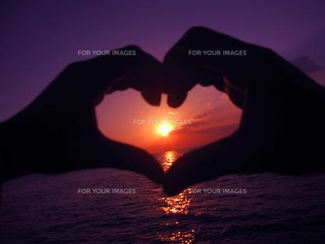 カップルの手のハートと海の夕日(暗め紫)の素材 [FYI00243338]