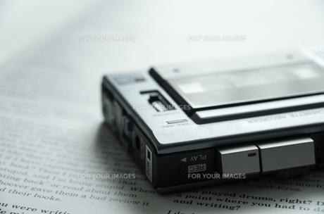 本の上に置いたマイクロカセットレコーダーの素材 [FYI00244687]