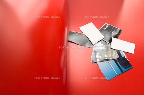 赤いページ上の破られた写真の写真素材 [FYI00244703]