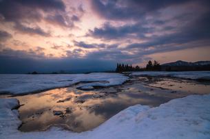 雪解けを待つ、朝焼けを映す山の田んぼの素材 [FYI00245757]
