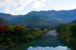 土佐高知の美しい山々と川。特急列車が鉄橋を通り過ぎて行くの写真素材 [FYI00247123]