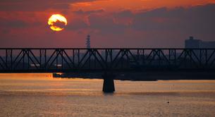朝焼けの中、鉄橋を輪ってきた列車の写真素材 [FYI00247178]