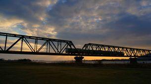 オレンジ色に輝いてきた空と鉄橋を渡ってきた列車の写真素材 [FYI00247196]