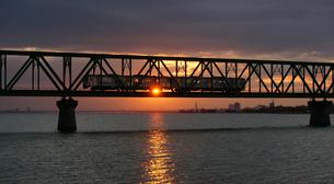 朝日の中を通り抜けていく列車の写真素材 [FYI00247199]